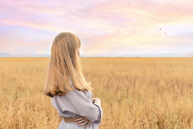 Девушка стоит в пшеничном поле с великолепным закатом на заднем плане