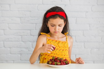 Girl standing in front of wall taking strawberries from white plate on desk