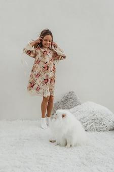 Девушка стоит в постели и играет с собакой