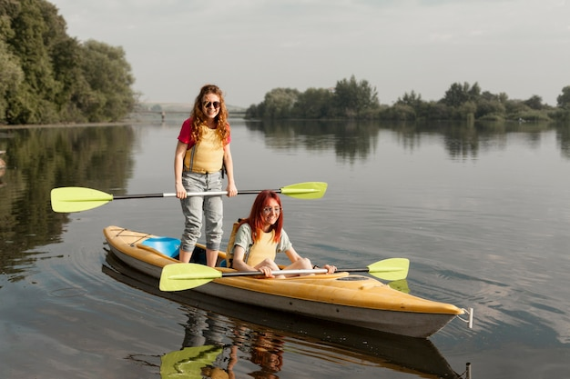 Girl standing in kayak with friend