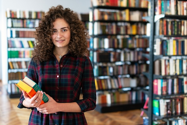 Girl  standing in the library holding books in her hands against the backdrop of a rack of multi-colored books