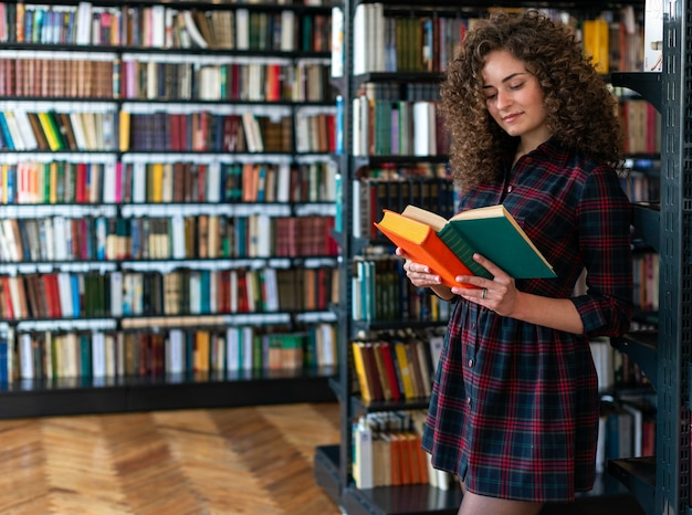 Girl  standing in the library holding books in her hands