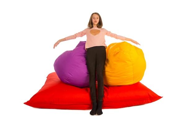 白で隔離されるお手玉の椅子とお手玉のソファの近くに立っている女の子