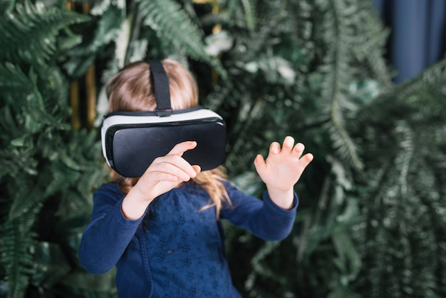 Girl standing near the plants wearing virtual reality glasses touching the hands in air