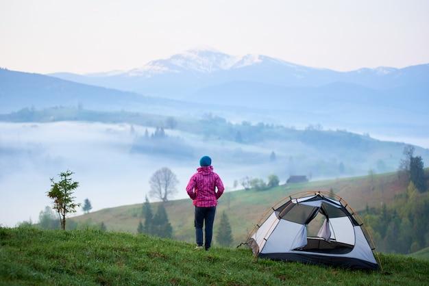 Girl standing near tourist tent on grassy hill