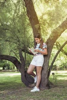 Girl standing near tree reading