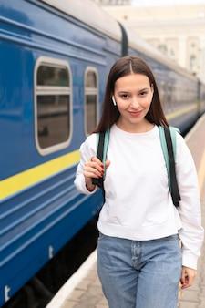 Девушка стоит рядом с поездом вид спереди
