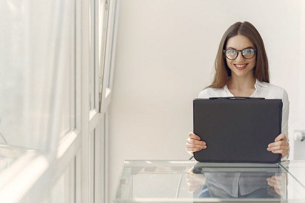 Girl standing in the office with a laptop