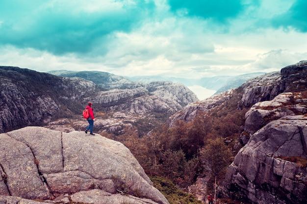 Девушка стоит на большом валуне и смотрит на норвежский фьорд