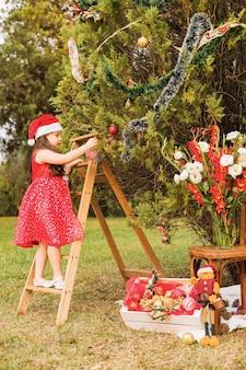 階段に立っている女の子がクリスマスツリーを飾る