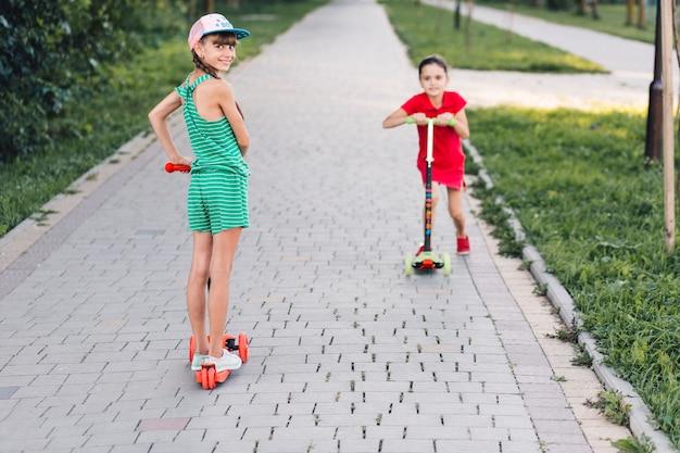 공원에서 산책로를 타고 그녀의 친구와 함께 푸시 스쿠터에 서있는 소녀
