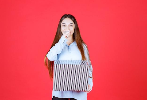 빨간 벽에 서서 은색 선물 상자를 들고 있는 소녀.