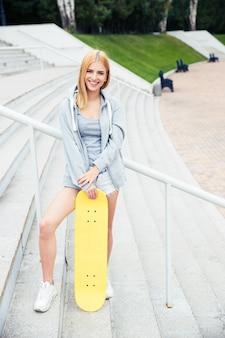 Девушка стояла на лестнице со скейтбордом