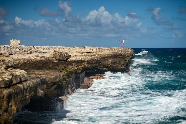 Девушка стоит на берегу залива дьявольского моста - карибское тропическое море - антигуа и барбуда. понятие свободы и власти