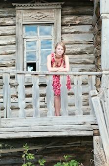 오래 된 목조 주택 현관에 서있는 여자