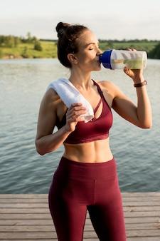 훈련 후 강둑에 서있는 소녀. 그녀는 레몬과 함께 물을 마시고