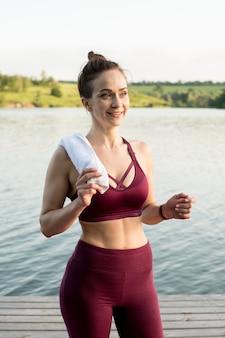 훈련 후 강둑에 서있는 소녀. 그녀는 웃고