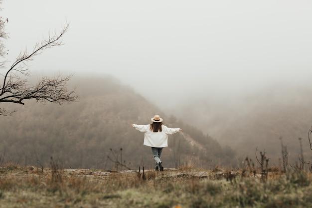소녀는 돌에 서서 산에 안개 속에서 소나무와 풍경을 즐깁니다.
