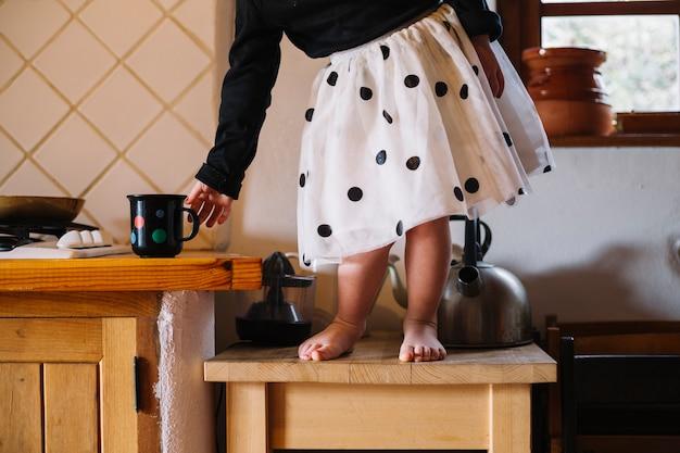 Девушка, стоящая на верхней части табурета, держащая чашку