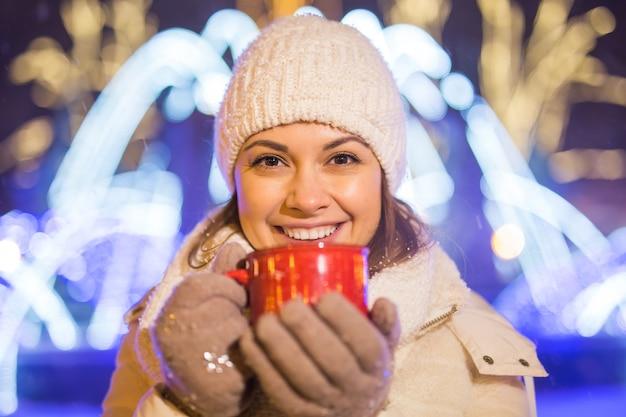 겨울 크리스마스 도시 배경 눈이 드리프트 위에 서 있는 소녀는 따뜻한 재킷 모자를 서고 뜨거운 차 음료와 함께 컵 차를 들고 있습니다.