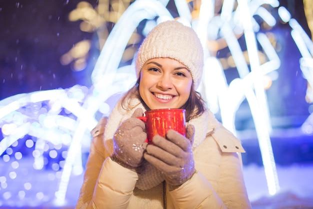 겨울 크리스마스 도시 배경 위에 서 있는 소녀 눈 눈 드리프트 스탠드 따뜻한 재킷 모자 보유
