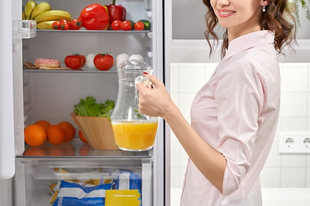 Девушка стоит холодильник и держит кувшин с соком.