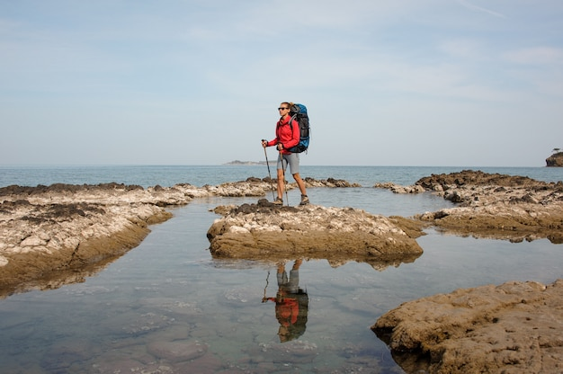 Girl standing on the rock on the sea with hiking backpack