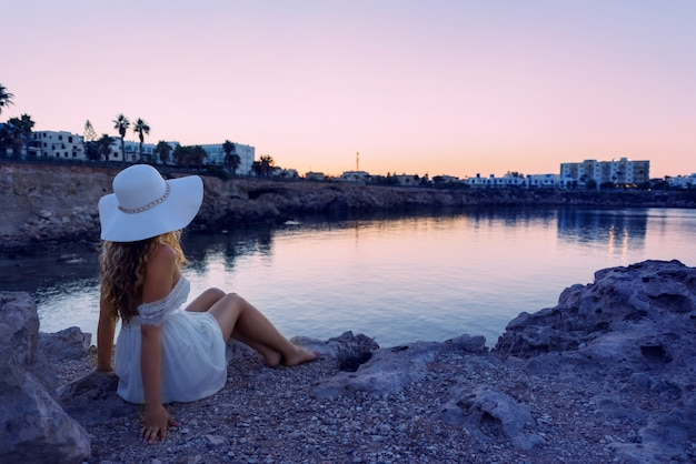 Girl standing on a shore watching sunset. beautiful beach on a tropic island. cyprus protaras