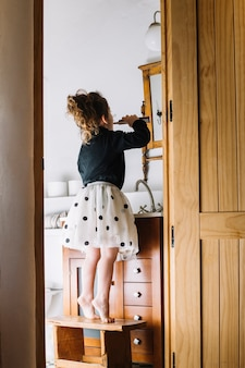 Girl standing on stool with toothbrush looking at mirror