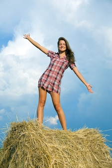 Girl standing on straw bail