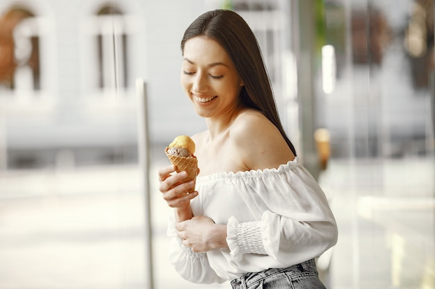 Girl standing in a summer city with ice cream