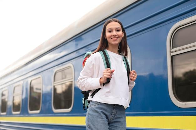 Ragazza in piedi accanto alla vista bassa del treno