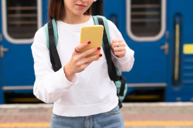 Girl standing next to the train medium shot