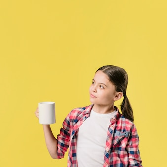 Girl standing with cup in studio