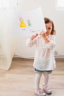 Girl standing with drawing of mother and child