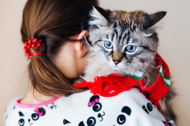 Girl stands back and holds the cat in her arms