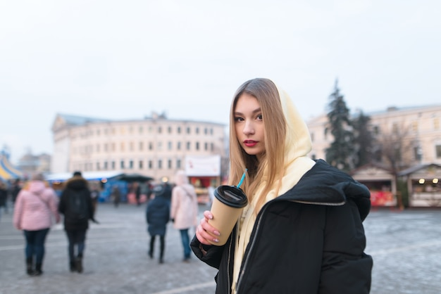 Girl stands in the background of a city's winter street with a cup of coffee