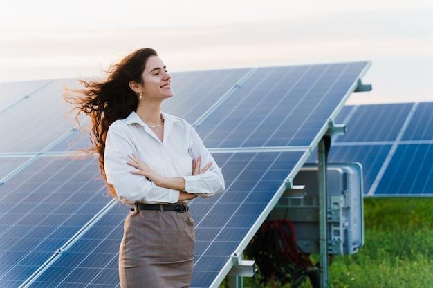 Девушка стоит рядом с рядами солнечных батарей на земле