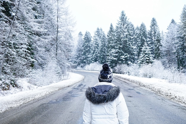 A girl stands on a deserted road around tall trees. people on a winter road. dreams of travel. winter trip