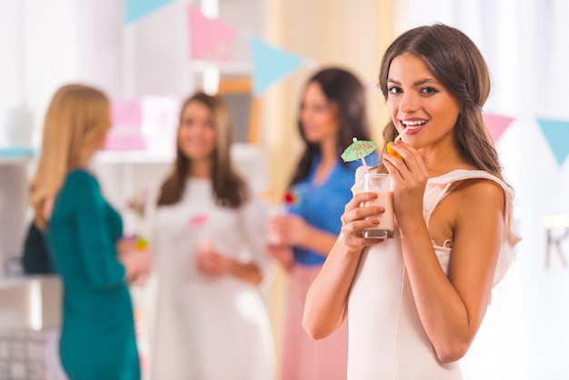 Girl stands drinking a cocktail and smiling at front