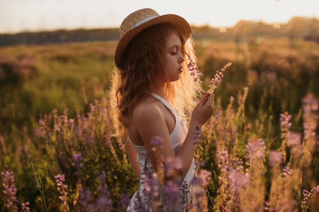 Girl stands in a field of flowers at sunset in summer
