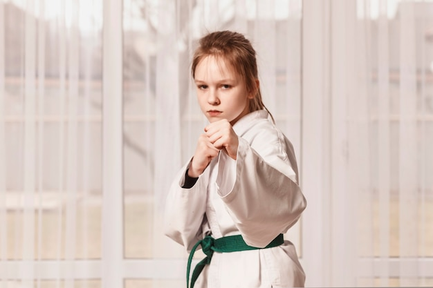 The girl stands in a fighting stance and looks at the camera