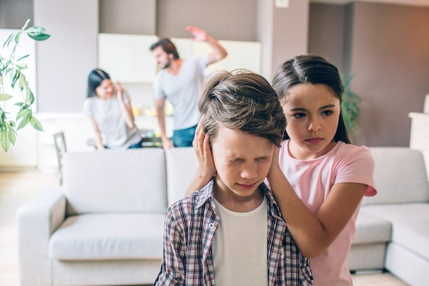 Girl stands behind her brother and keeps his ears closed with hands. boy is terrified. he has eyes closed. woman is trying to protect herself. guy is going to beat her. he holds his hand up.