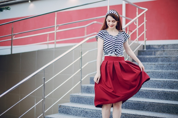 Girl in a stands holding her red skirt