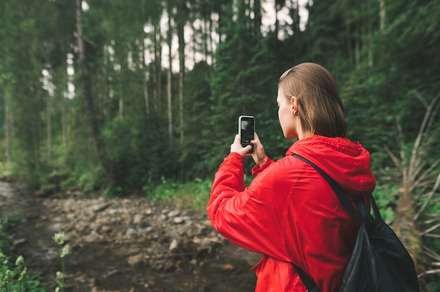 소녀는 산 강 근처의 숲에 서서 스마트 폰으로 풍경 사진을 찍습니다.