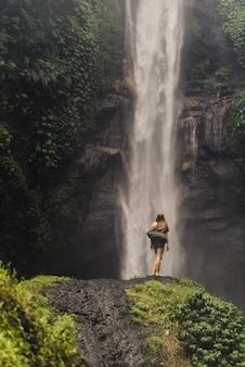 Девушка стоит перед огромным водопадом