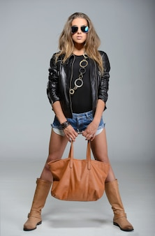 A girl stands in a leather jacket with a bag.