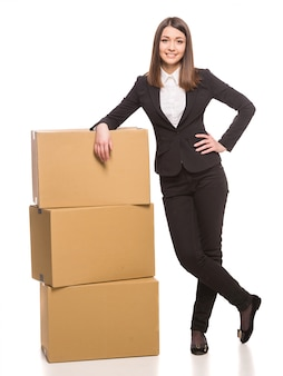 The girl stands near the boxes and posing.