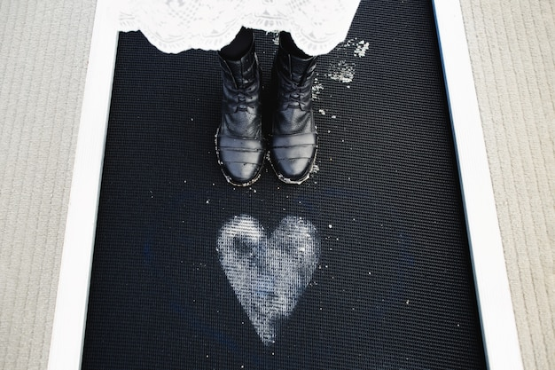 The girl stands near the painted heart on the floor
