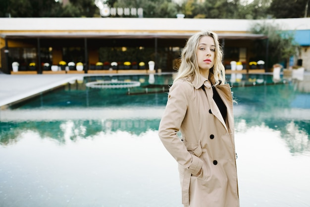 A girl stands near a pool in luxury hotel